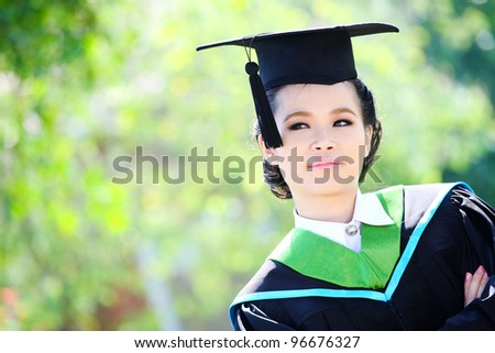 Asian girl graduation looking up outdoors - stock photo