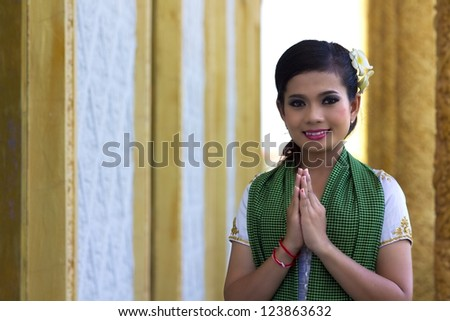 Asian Girl Greets in temple traditional way with both hands - stock photo
