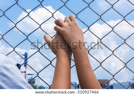 asian girl hand hold jail - stock photo