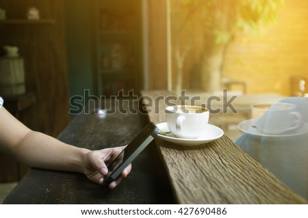 Asian Girl hand holding smart-phone with coffee cup on wooden table with cross process and soft flare filter - stock photo