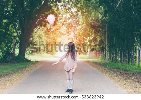 Asian girl holding a balloon on the road in the park.