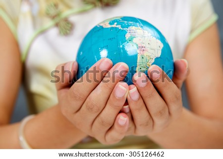 Asian girl holding a globe in his hands - stock photo