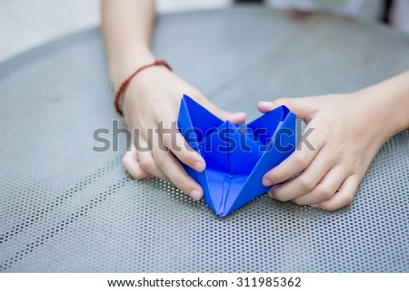 Asian girl holding a paper boat outdoors on sunny summer day - stock photo