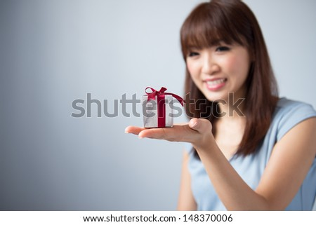 Asian Girl Holding Gift Box and Smiling, cute Asian beauty model, isolated on blue background - stock photo