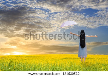 Asian girl holding pink umbrella in grass field and sunset - stock photo