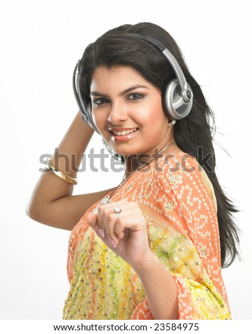 Asian girl in sari listening to music with head phones - stock photo