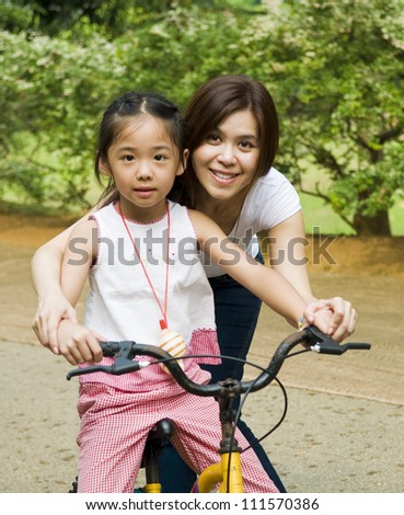 Asian girl learns to ride a bicycle - stock photo