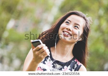 Asian Girl Listening Music at Park - stock photo