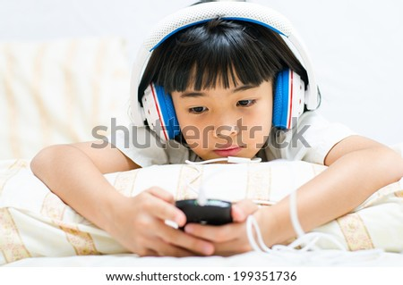 Asian girl listens attentively to the music by phone.