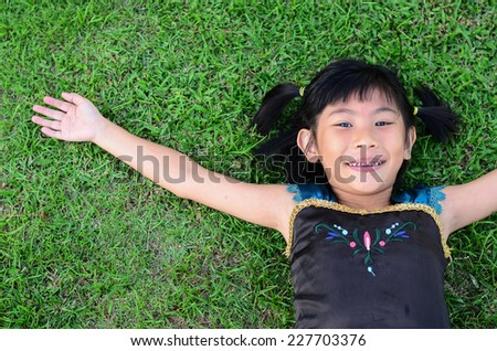 Asian girl lying on grass hand rise her hand. - stock photo