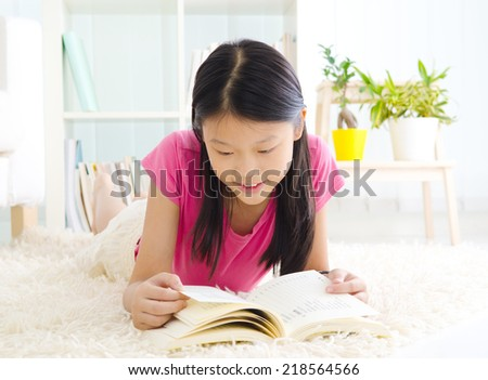 Asian girl lying on the carpet and reading a book - stock photo