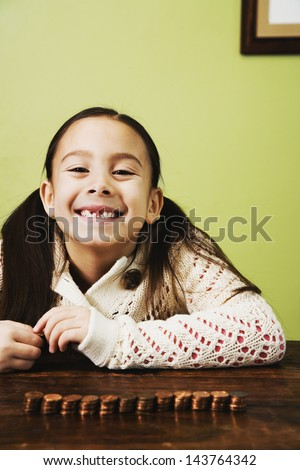 Asian girl next to stacked coins - stock photo