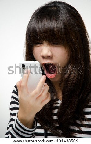 Asian girl on black and white shirt is yelling to the smart phone - stock photo