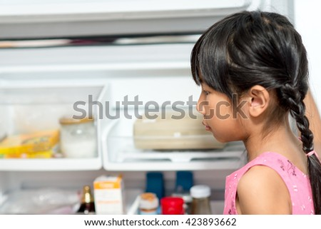 Asian girl open refrigerator and looking for something for eat