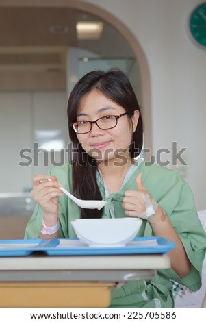 Asian girl patient Enjoying Meal In Hospital Bed - stock photo
