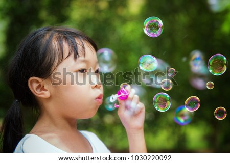 Asian girl play a bubble in nature, this picture can use for kid, nature, play, child. and summer concept