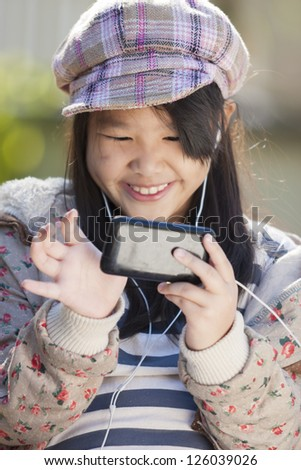 Asian girl play game from Smart phone - stock photo