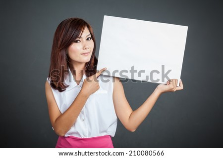 Asian girl point to blank sign on gray background