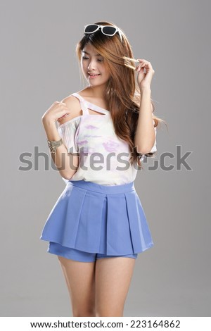 Asian girl posing in Sexy White shade Lady Singlet Top with blue skirt shorts.