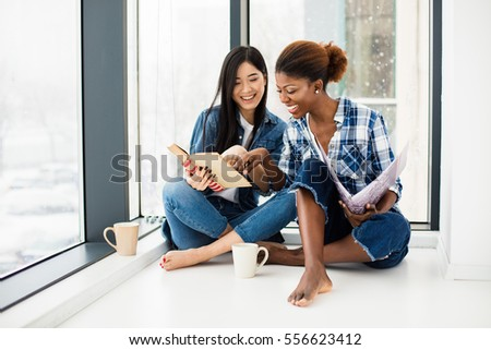 asian girl reading and studing with her afro american friend, concept of different ethnicity
