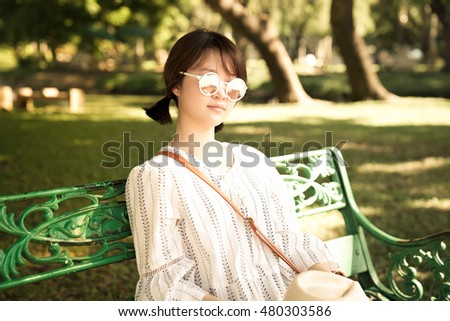 Asian girl reads a book  in the park with hat and sun glass.