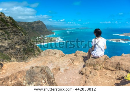 Asian girl relazxing and watching fabulous top view of Big Island on the cliff, Hawaii USA - stock photo