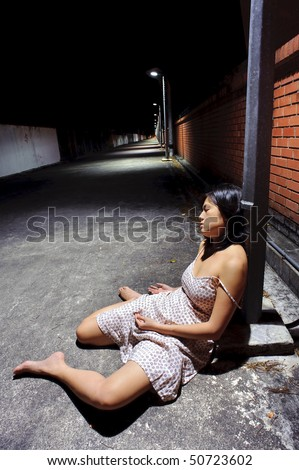 Asian girl rests against a street lamp