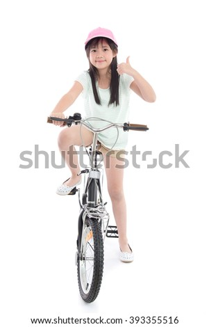 Asian girl riding a bike and showing thumb on white background isolated