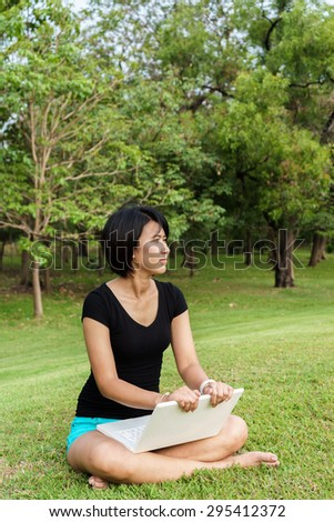 Asian girl sit on the green grass in park and relax with laptop - stock photo