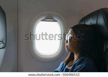Asian girl sitting beside airplane window