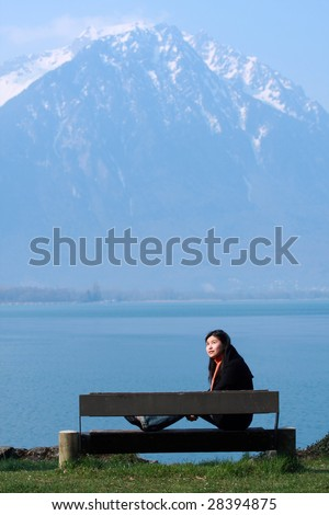 asian girl sitting in front of lake in the beautiful nature
