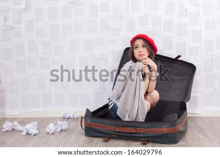 asian girl sitting in old vintage traveling suitcase, wanting to go travel - stock photo