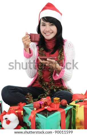 asian girl smiling and carrying a cup of tea in front of Christmas gifts, isolated on white
