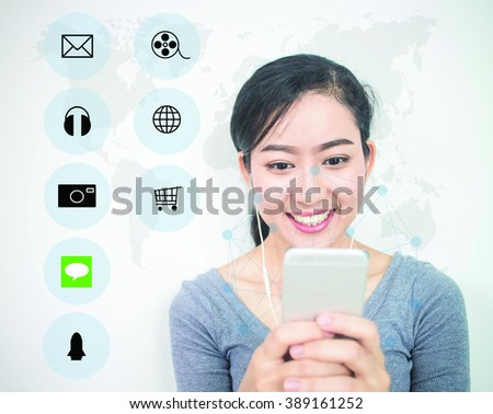 Asian girl smiling so happy using a blur smart phone with modern technology and digital layer effect with icons over blur World map. business strategy concept. (Selective focus) - stock photo