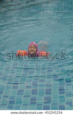 Asian girl swimming in swimming pool with arm floats, soft and selective focus