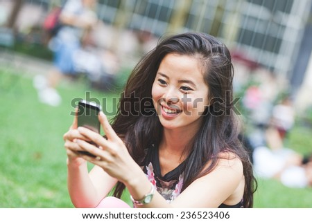 Asian Girl Typing on Smart Phone at Park - stock photo