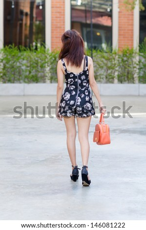 Asian girl walking away in park
