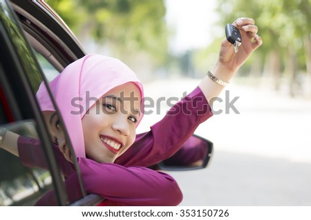 Asian Girl wearing hijab  Driving Happy smiling in a red car holding car key