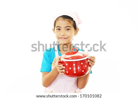 Asian girl wearing kitchen apron with pot - stock photo