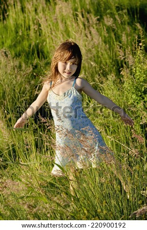 Asian girl with arms outstretched in meadow - stock photo