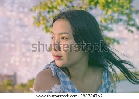 Asian girl with black hair on bokeh background in park in vintage tone style - stock photo