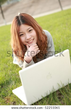 asian girl with laptop on grassland