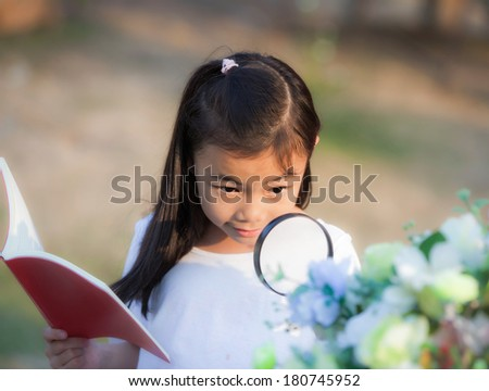 Asian girl with magnifying glass outdoors and note for flower description - stock photo