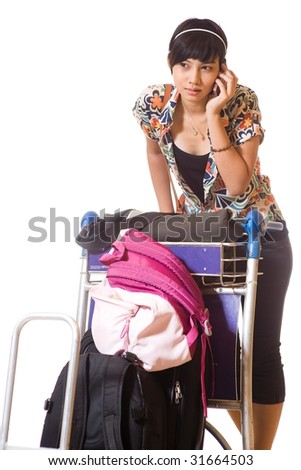 asian girl with trolley loaded with luggage and bags using mobile phone