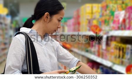 Asian girl, woman shopping snacks in supermarket - stock photo