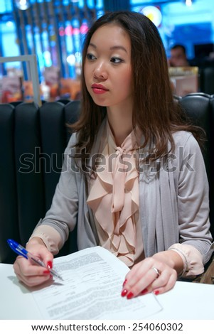 Asian girl writes and looks away. - stock photo
