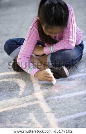 Asian girl, 7 years, playing outdoors, drawing pictures with sidewalk chalk - stock photo