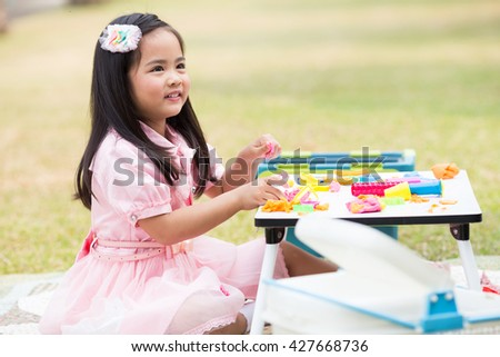 Asian girls have fun playing with clay - stock photo