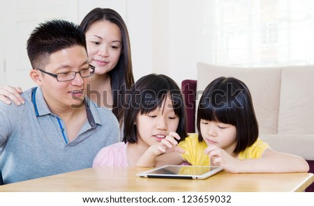 Asian girls sharing information on tablet computer - stock photo