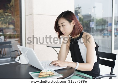 Asian girls use tablets.In a street cafe